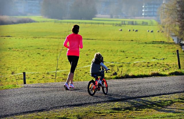 běžící matka s dítětem na kole